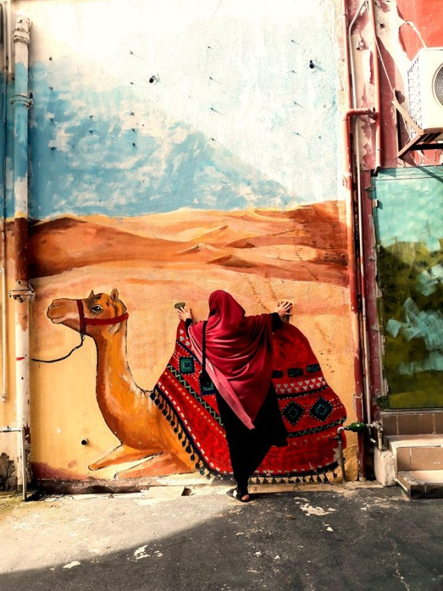 Sie versucht, auf ein gemaltes Kamel zu steigen.
